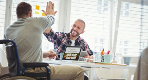 man in wheelchair high-fiving coworker in office